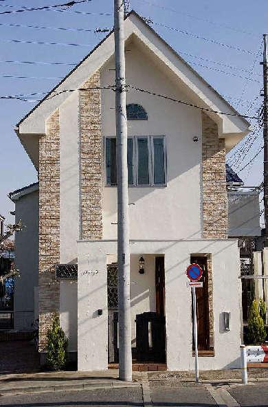 南欧風の煉瓦積み調タイルを隅角部に配し、シンプルな形の家のアクセントに