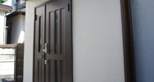 "<span class=""title"">タイルとガラスで囲まれた玄関を親子扉が入るように全面改装</span>"