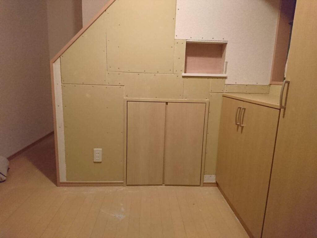 玄関前の壁に階段下収納を増設
